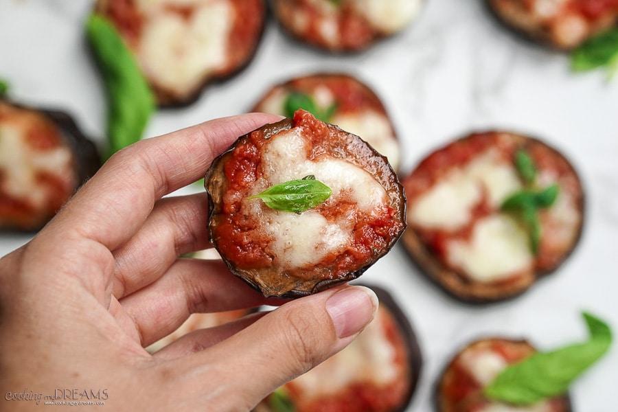hand holding a mini eggplant pizza slice