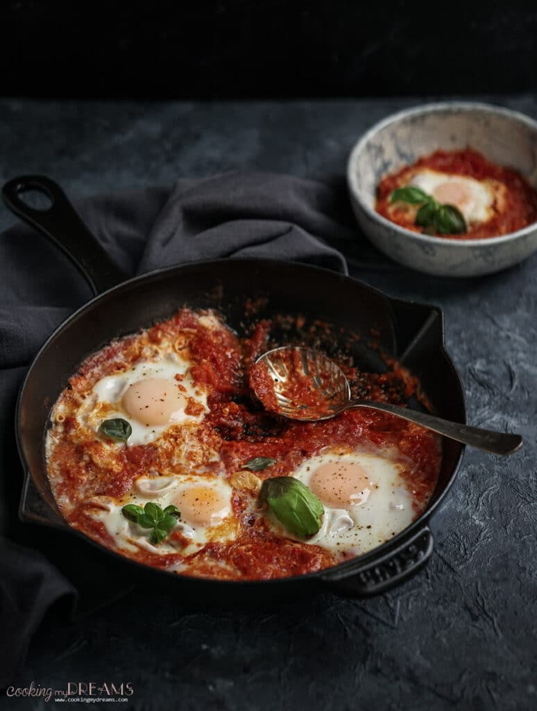 skillet with eggs in tomato sauce with a spoon and a portion in a bowl