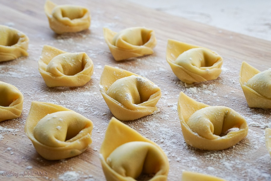 tortelloni lined up on a wooden board