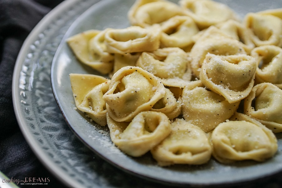 close up of tortelloni on a plate with parmigiano