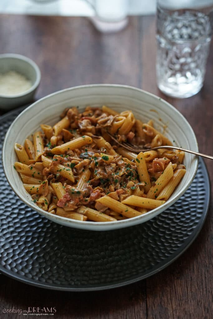penne alla boscaiola in a plate with fork