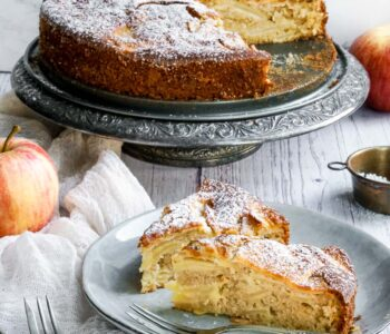 two slices of italian apple cake on a plate in front of the cake