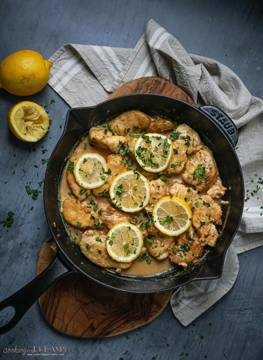 skillet with creamy lemon chicken and lemon slices