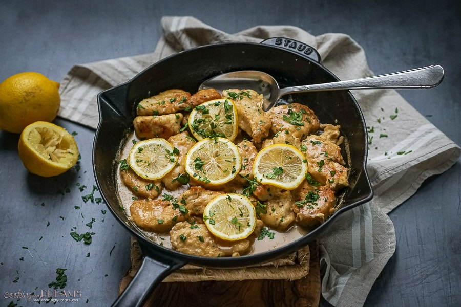 skillet with spoon scooping the lemon chicken