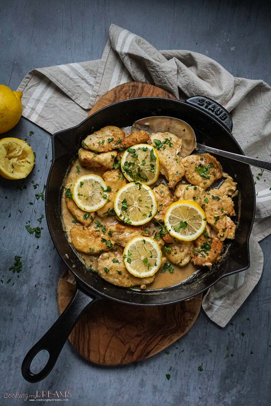 skillet with spoon and chicken with lemon slices