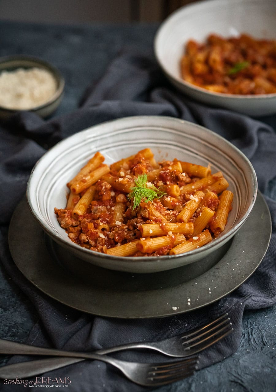 white dish with pasta with sausage tomato sauce