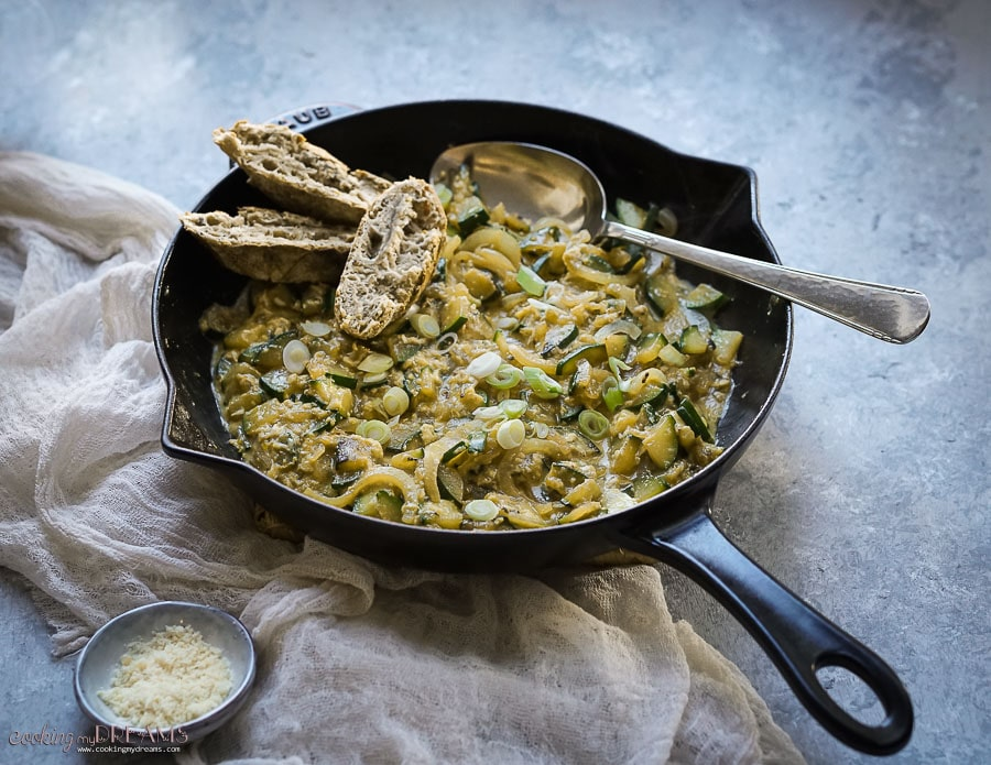 skillet with scrambled eggs, zucchini and onions with a spoon