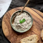 bowl of mushroom pate with spoon next to slices of bread