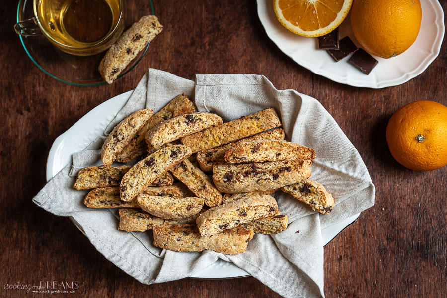 overhead of a tray full of chocolate orange biscotti with orange and a cup of tea on a side