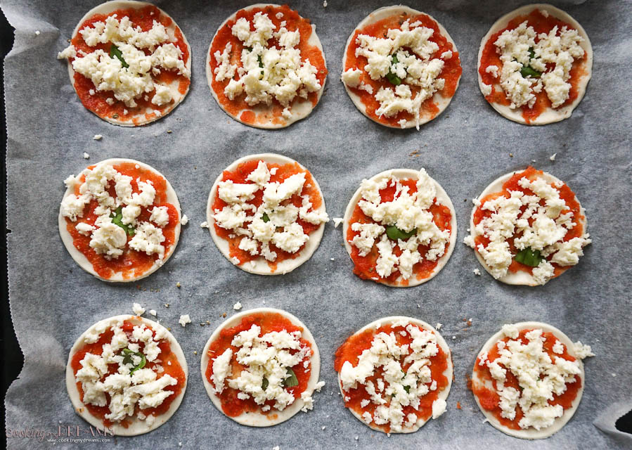 overhead of raw mini pizza on a baking sheet