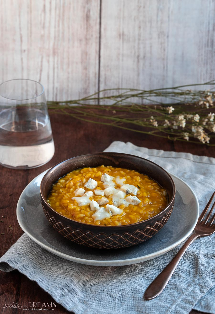 brown bowl with pumpkin risotto and gorgonzola cheese
