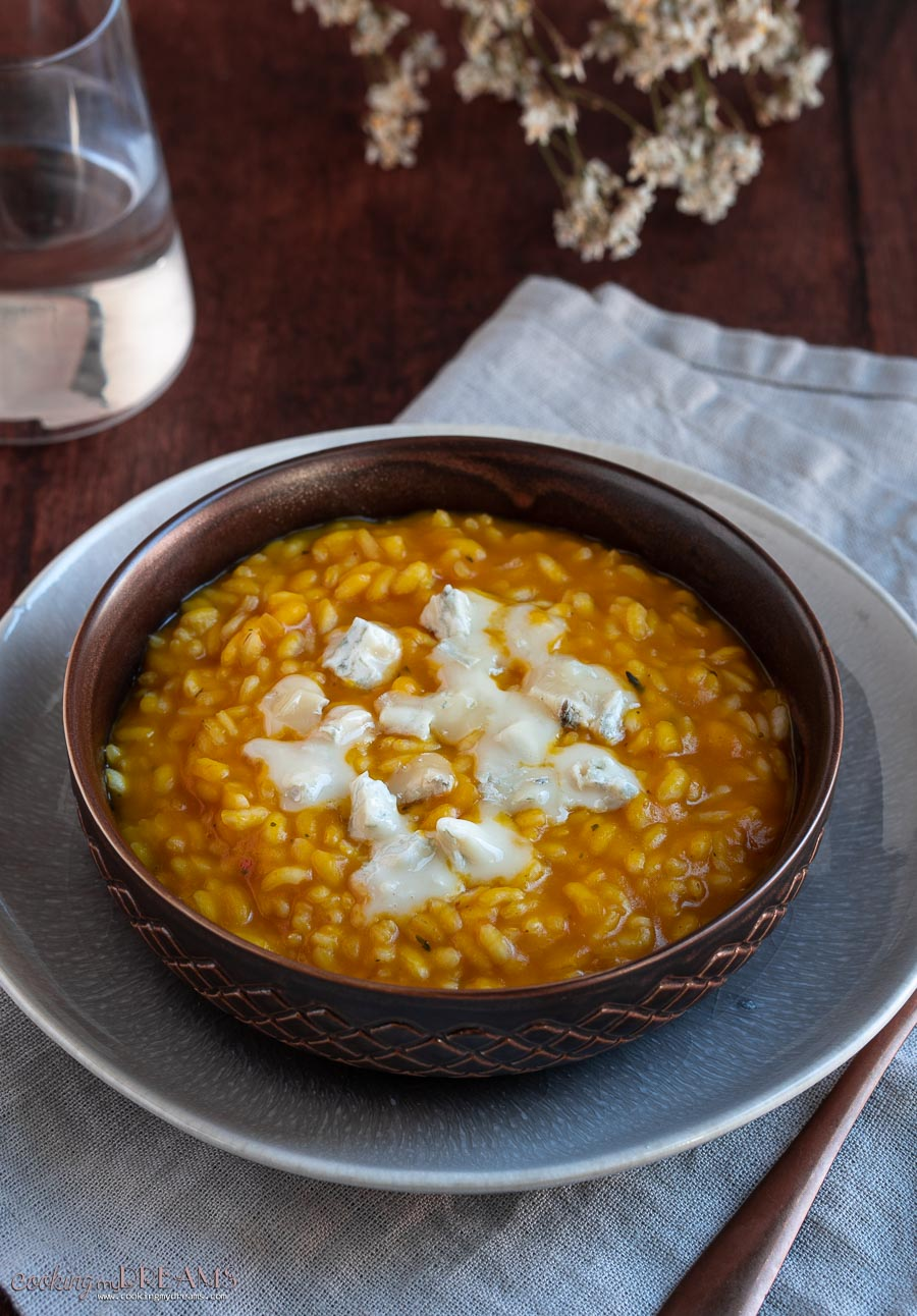 brown bowl with squash risotto and gorgonzola cheese