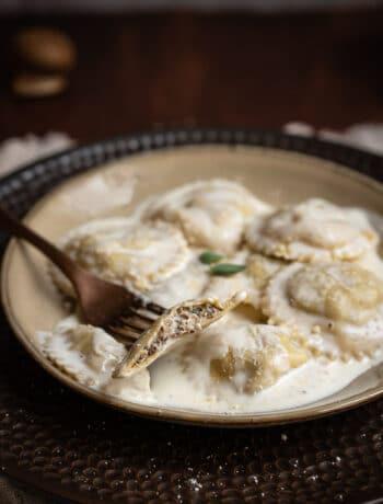 fork holding half mushroom ravioli on a plate
