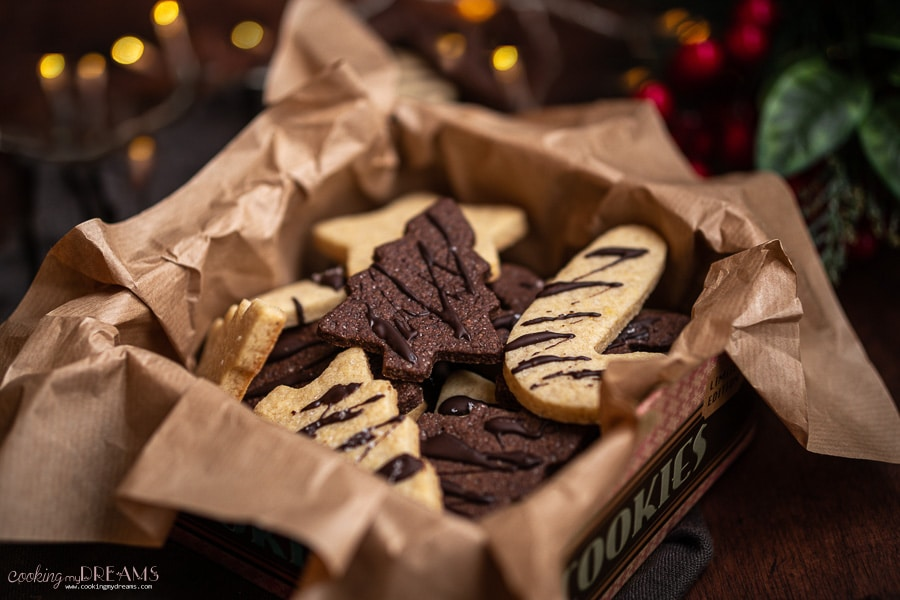 cookie box lined with paper full of vanilla and chocolate sugar cookies