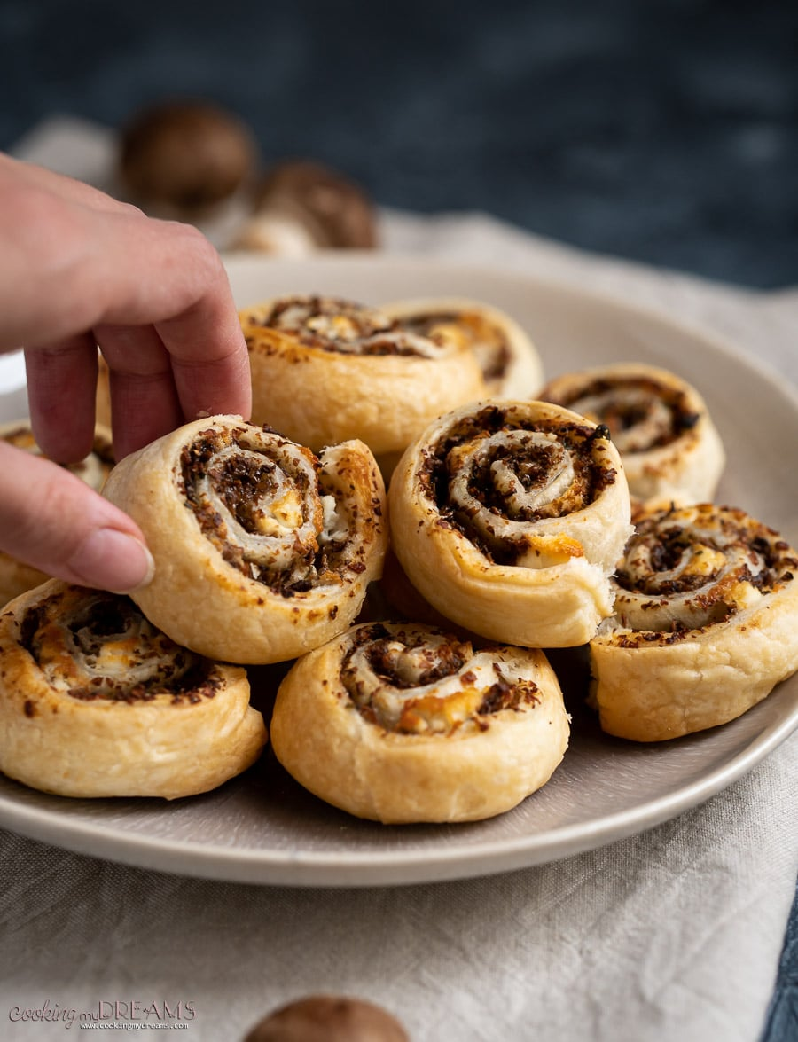hand taking one puff pastry pinwheels from a brown plate
