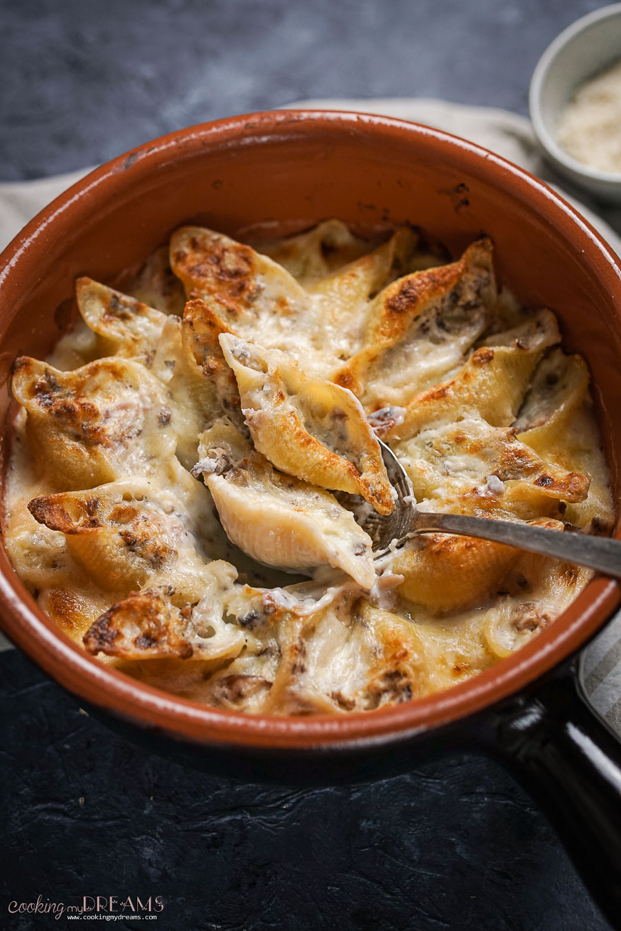 A spoon taking two stuffed shells from the baking dish to serve