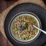 bowl with legumes and cereal soup and a spoon