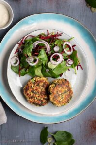overhead of plate with two salmon cakes and a salad