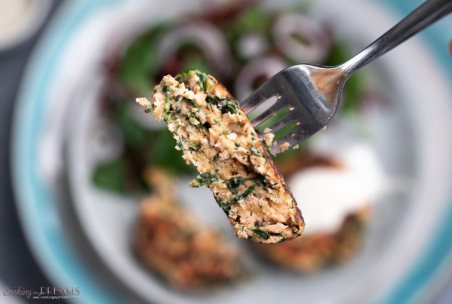 fork holding half spinach salmon cake