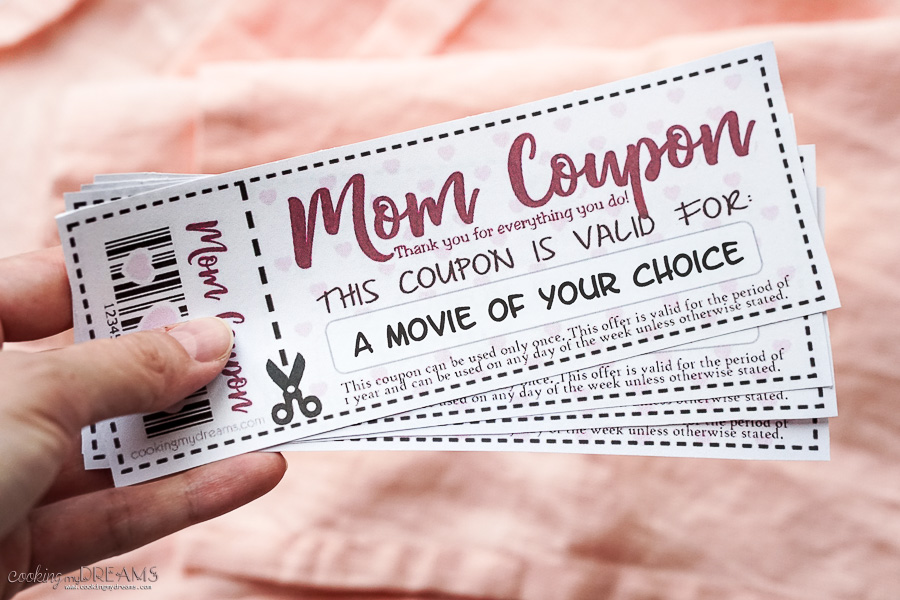 hand holding a bunch of customized mom coupons