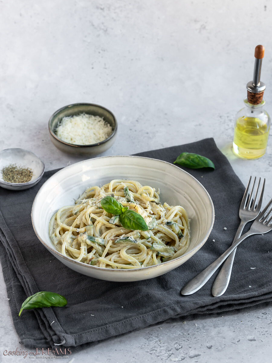 plate with creamy zucchini spaghetti on a towel next to forks and seasonings