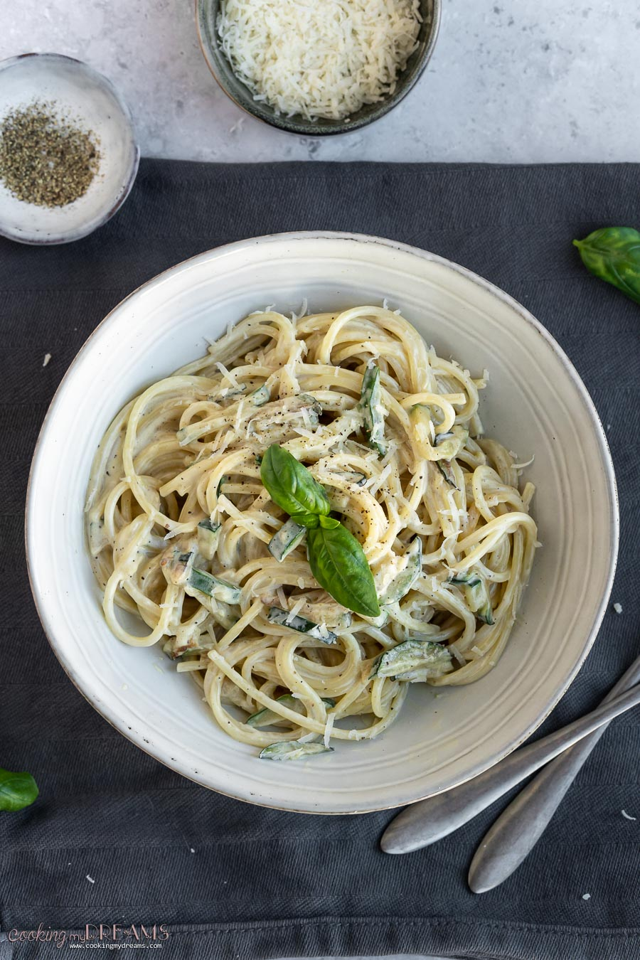 plate with creamy spaghetti with zucchini and basil leaves on top