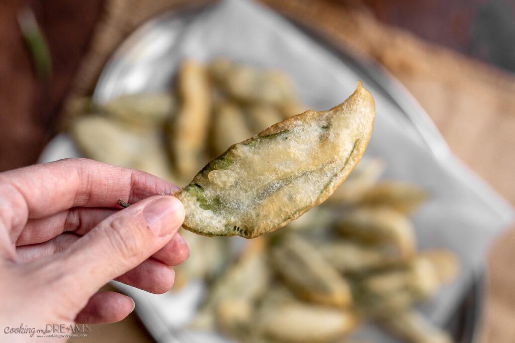hand holding a fried sage leaf