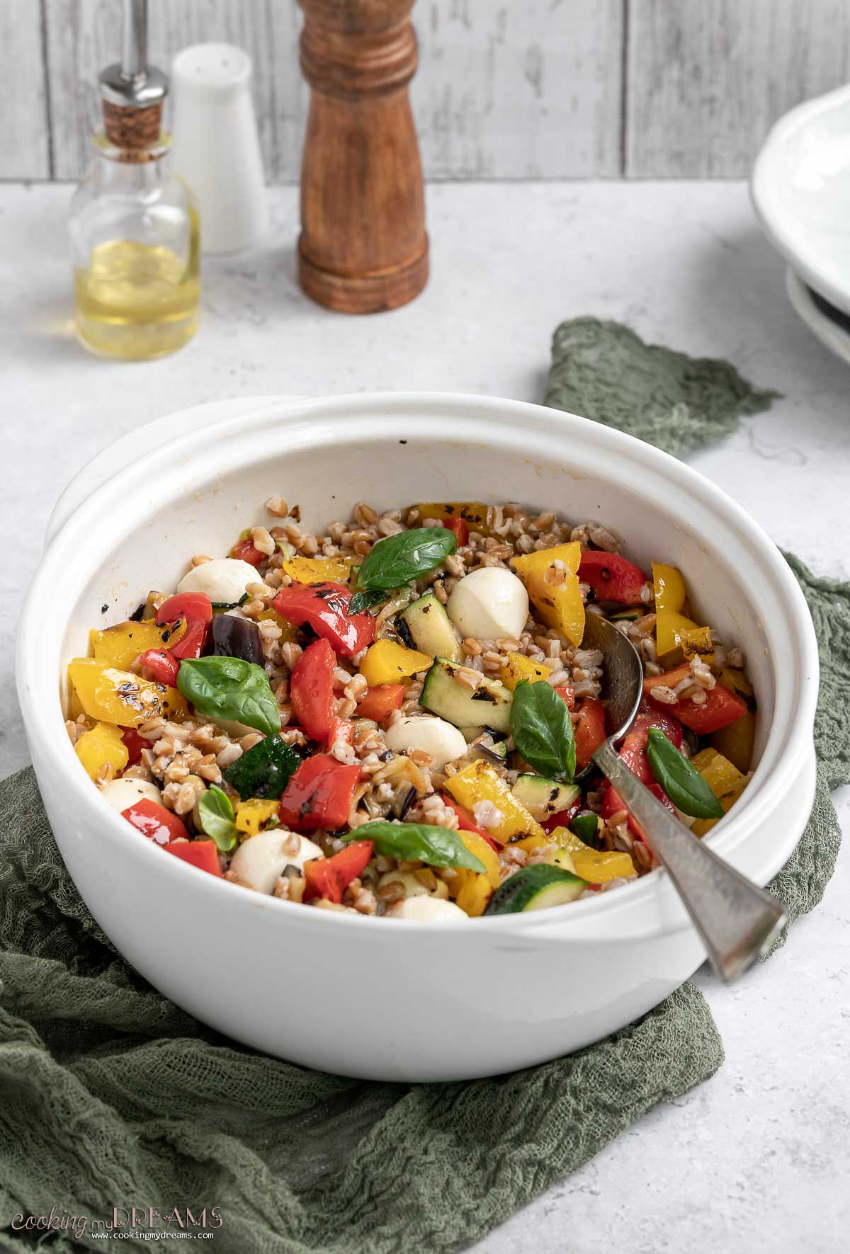 bowl of grilled vegetables farro salad with a spoon