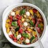 overhead of bowl full of grilled vegetables farro salad with a spoon