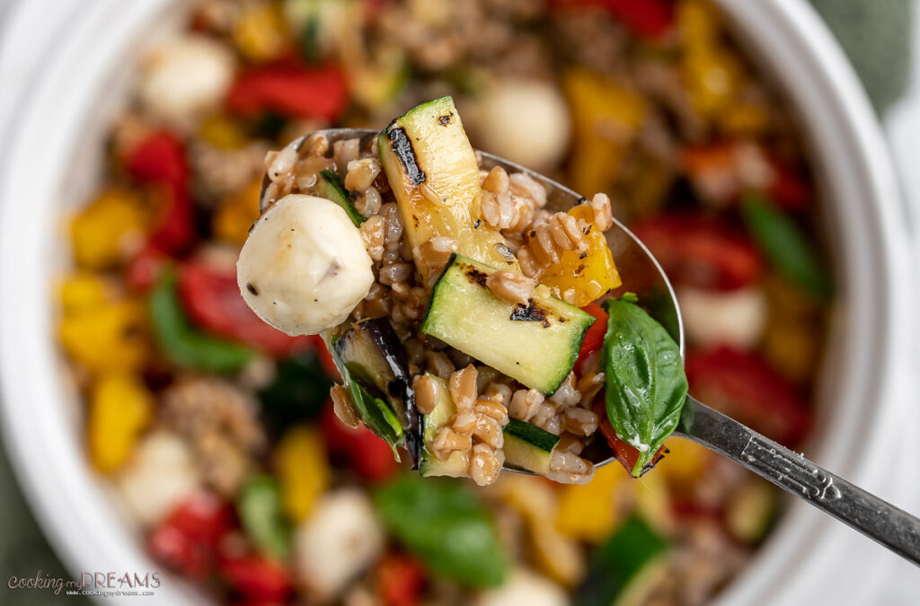 spoon taking some grilled vegetables farro salad from the bowl