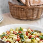 pasta salad in a serving plate next to a picnic basket