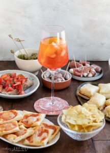 aperol spritz surrounded by foods and snacks on a table
