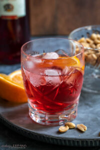 campari spritz in a glass next to orange slices and peanuts