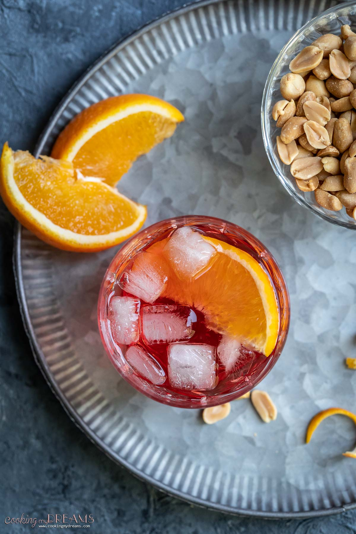 overhead view of a glass of campari spritz with ice and orange slices