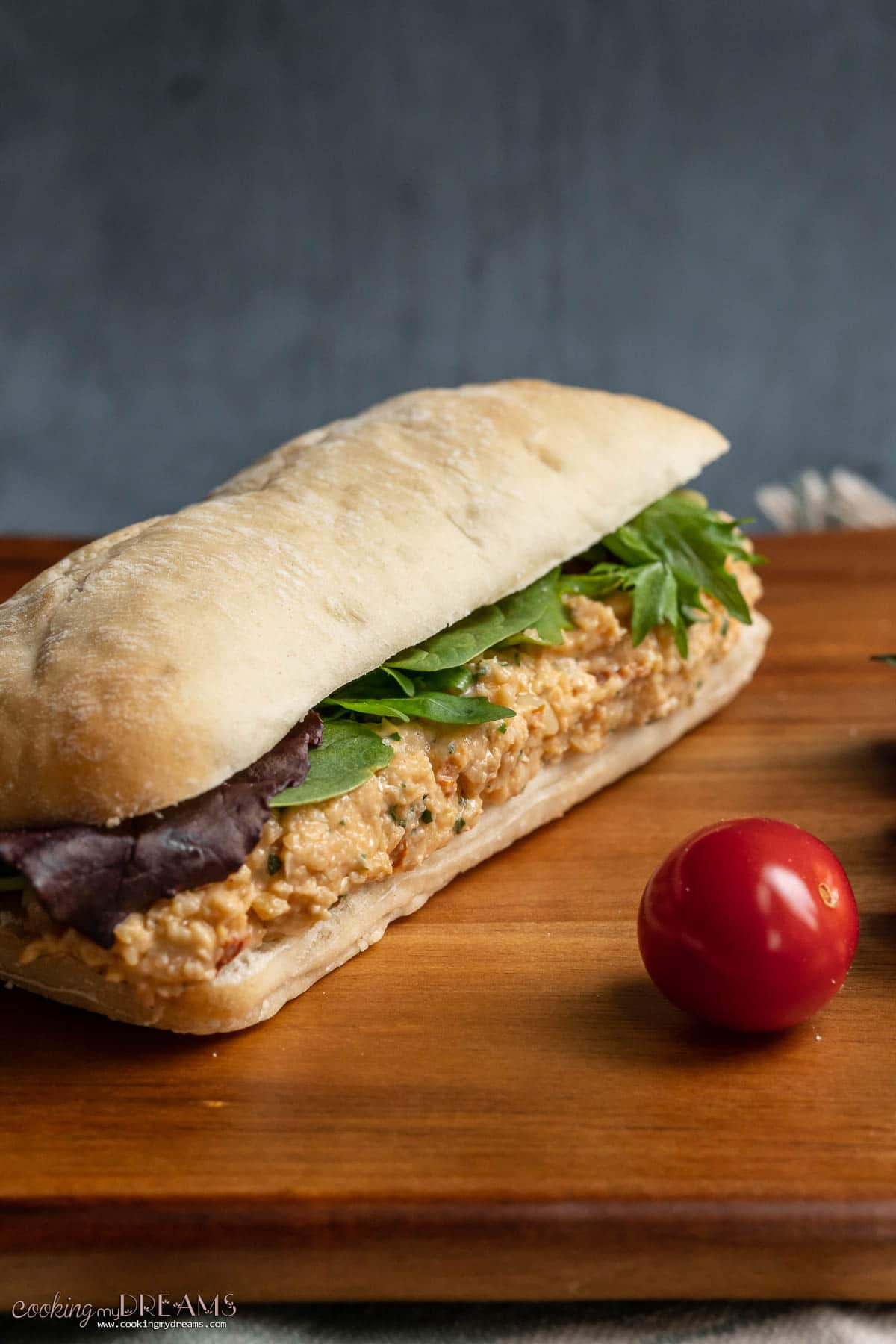 spicy chickpea salad sandwich on a wooden board