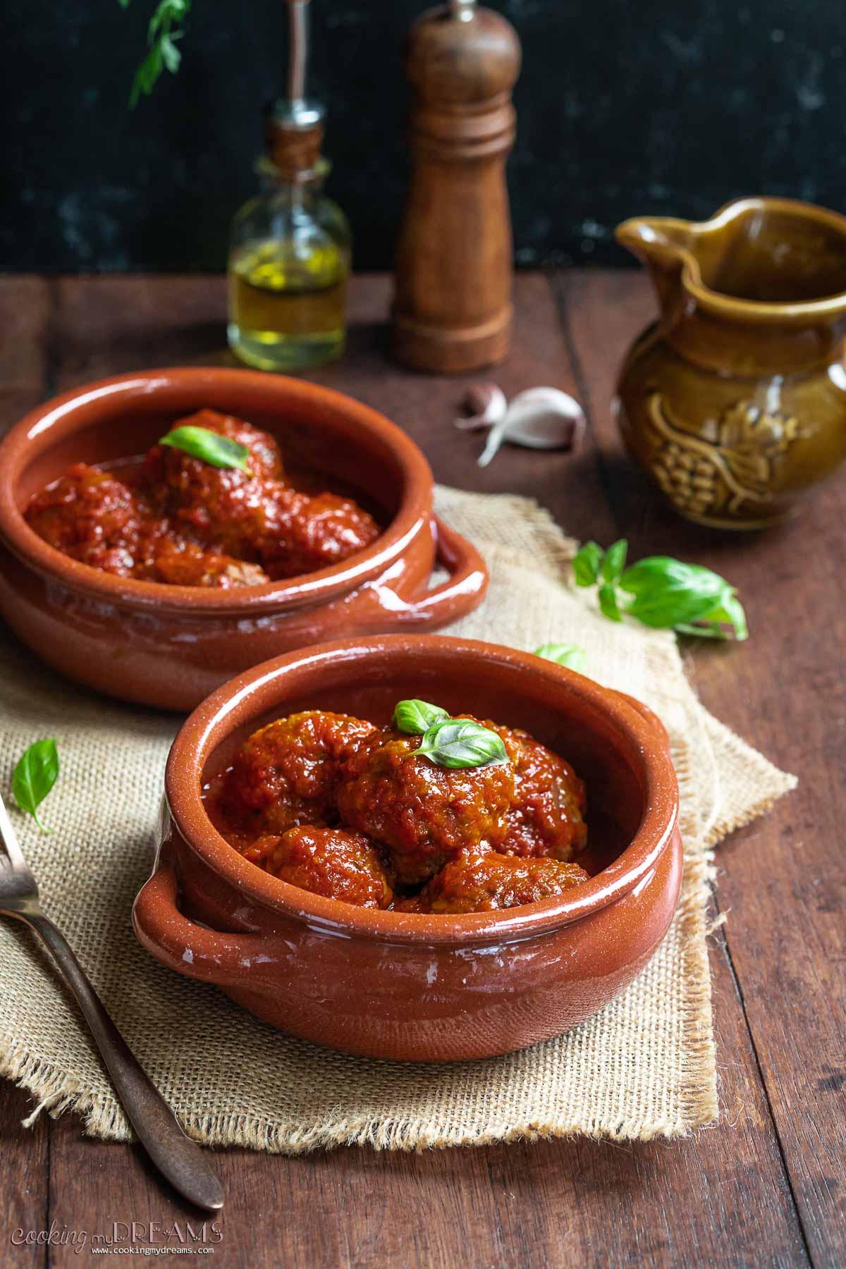 polpette al sugo served in terracotta bowls